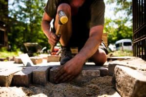 Garten und Landschaftsbauer bei der Pflastersteinverlegung